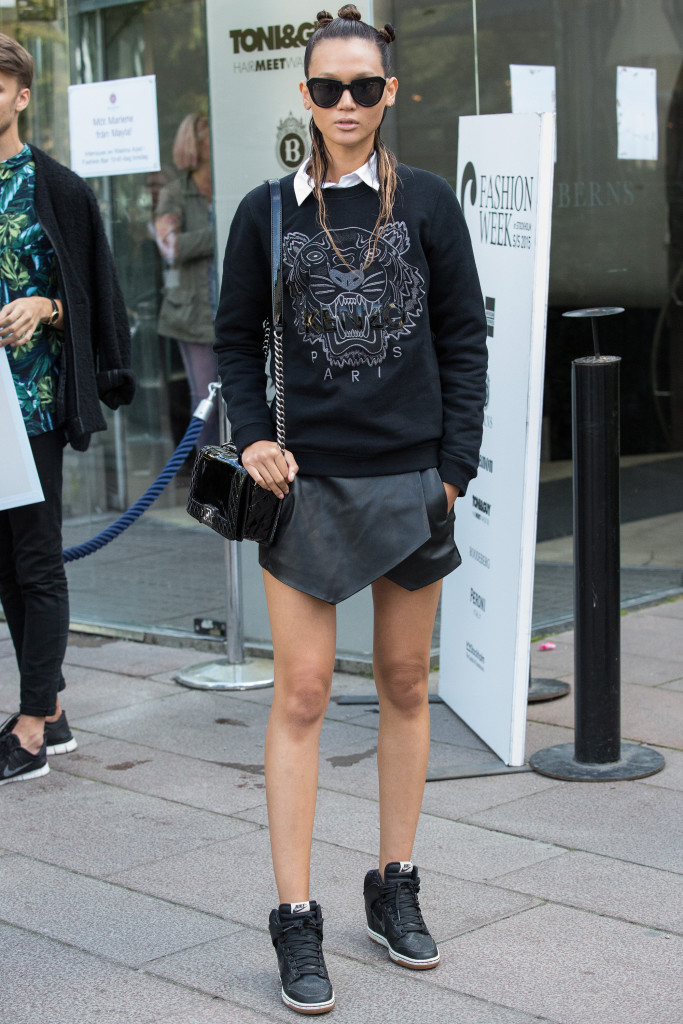 STOCKHOLM, SWEDEN - AUGUST 28: Model Miu Niyomsilpchai as seen between shows wearing a Kenzo sweater, shorts by Zara, a shirt by Back, shoes are from Nike and eyewear from Komono at Fashion Week on August 28, 2014 in Stockholm, Sweden. (Photo by Anna Lu Lundholm/Getty Images)