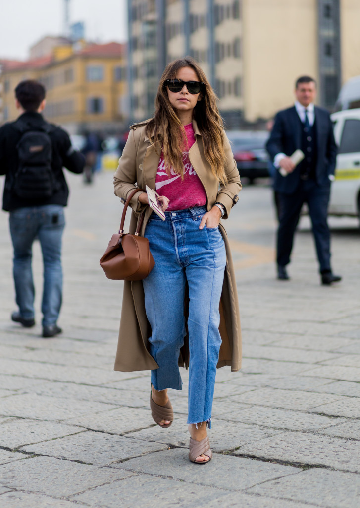 MILAN, ITALY - FEBRUARY 24:  Miroslava Duma wearing a trench coat a Coca Cola shirt, blue denim jeans, Gucci shoes and a Loewe bag seen outside Gucci during Milan Fashion Week Fall/Winter 2016/17 on February 24, 2016 in Milan, Italy (Photo by Christian Vierig/Getty Images)