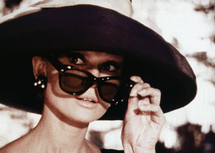 1961:  Belgian-born actor Audrey Hepburn (1929 - 1993) lowers her sunglasses in a still from director Blake Edwards' film, 'Breakfast at Tiffany's.'  (Photo by Paramount Pictures/Fotos International/Getty Images)