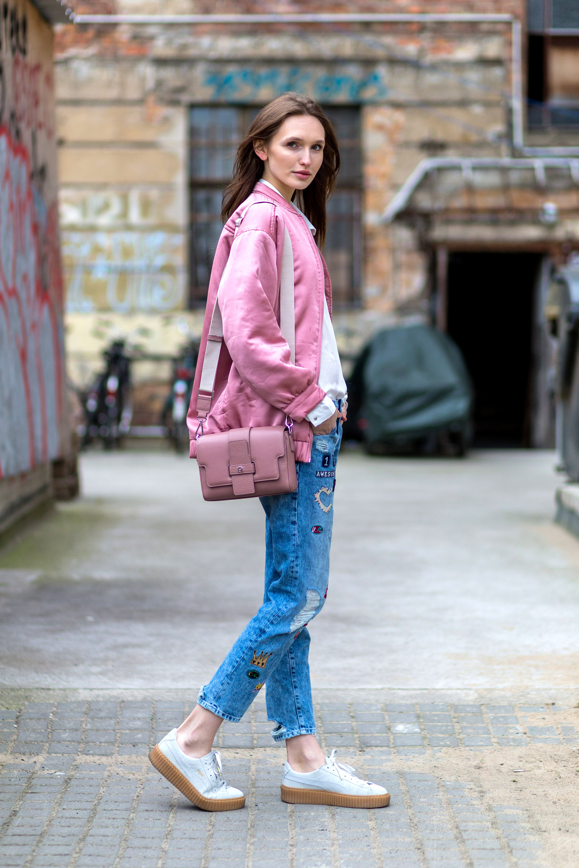 BERLIN, GERMANY - APRIL 8: Fashion model Anna Wilken is wearing a blue Zara denim jeans with patches, an oversized pink Mango bomber jacket, a pink Aigner Munich bag, white Puma creeper and a white Vero Moda blouse on April 8, 2016 in Berlin, Germany (Photo by Christian Vierig/Getty Images)