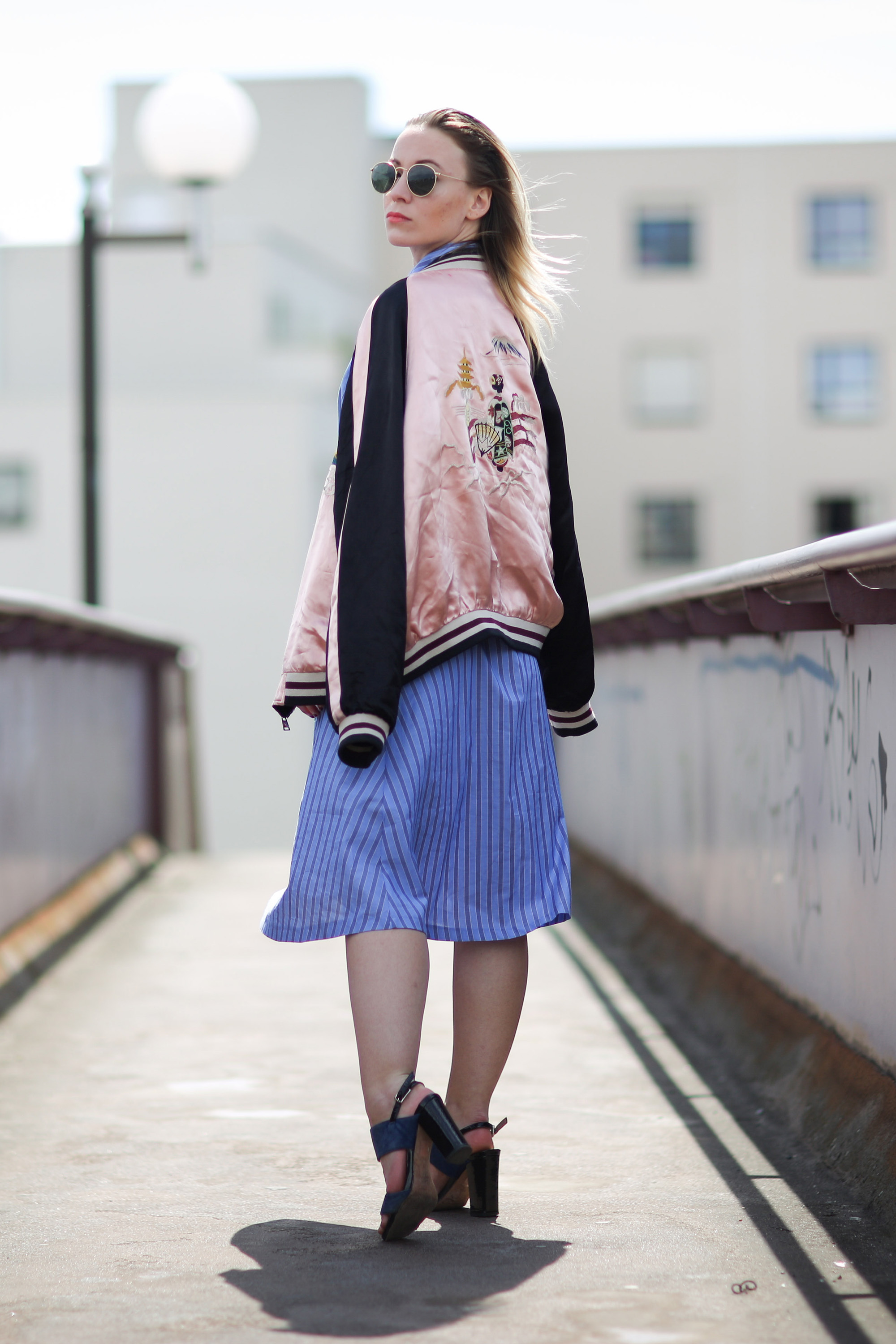 PARIS, FRANCE - MAY 08:  Amelie Lloyd (fashion blogger @ameetslloyd), is wearing a Sandro blue dress, Comptoir des Cotonniers blue shoes, a Zara black and pink bombers coat, Ray Ban sunglasses, and a Balenciaga bag, during a street style session,  on May 08, 2016 in Paris, .  (Photo by Edward Berthelot/Getty Images)