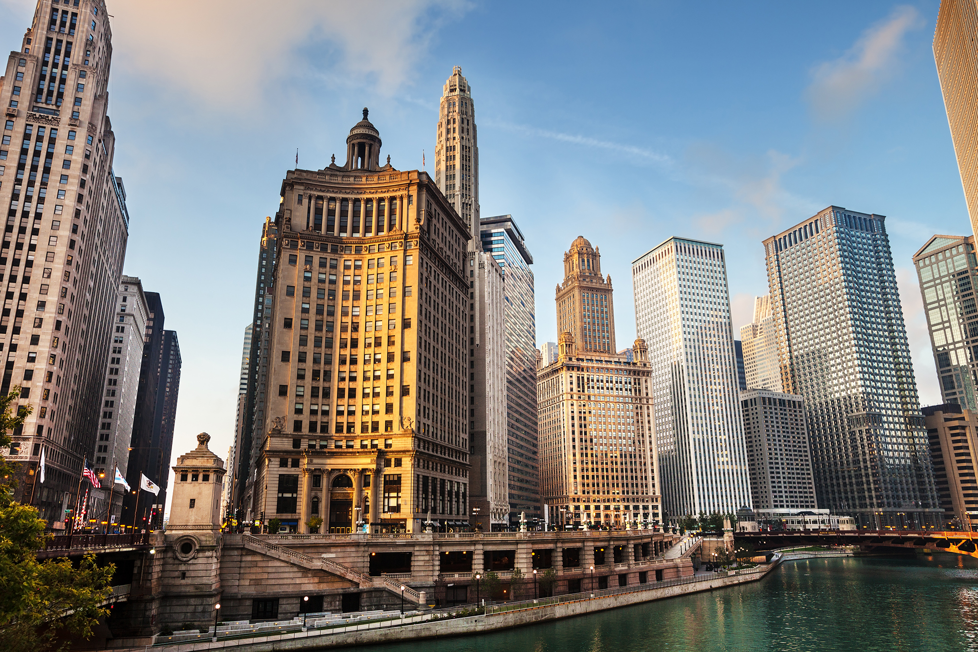 Early Morning, just after sunrise,  downtown Chicago. Wacker Drive on the Chicago River. Left is Michigan Avenue Bridge. Left to right are the London Guarantee and Accident Building, Mather Tower, Jewelers Building, and Unitrin Building. One or two background people.