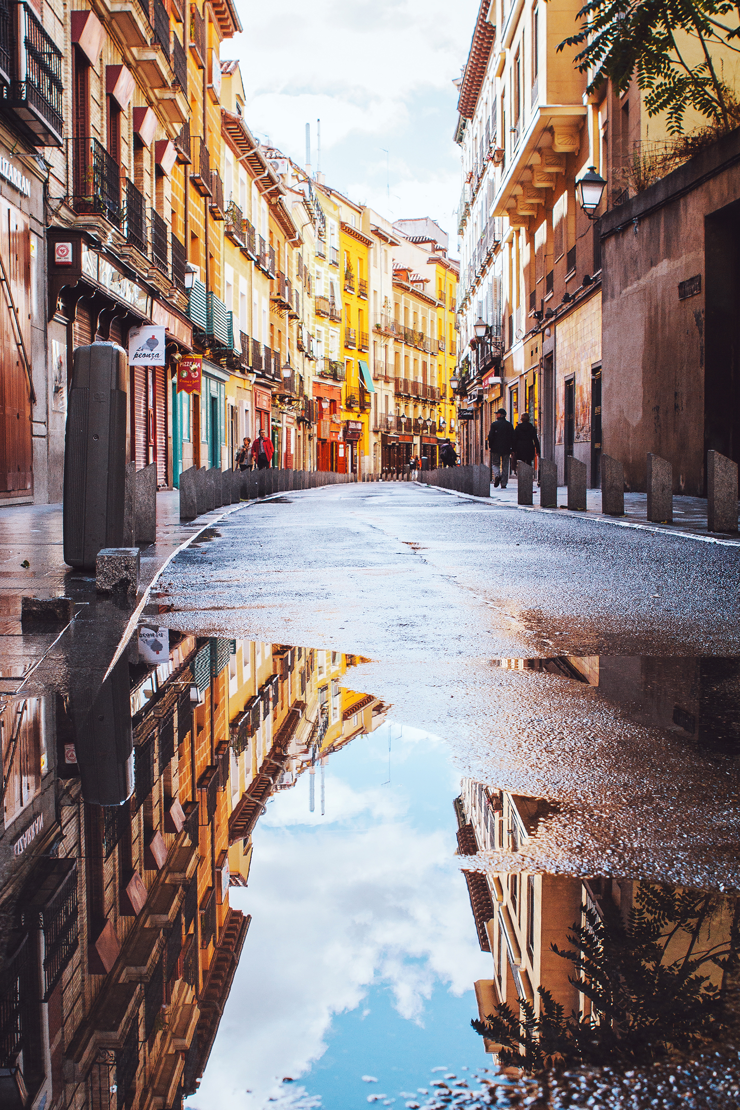 Colorful buildings in Madrid (calle Cava Baja) reflected in a big puddle.